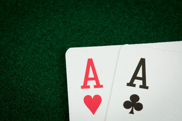 A close of shot of two aces on a green poker table