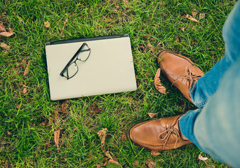 notebook and glasses on the green grass