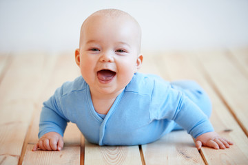Cute happy baby boy crawling on the floor