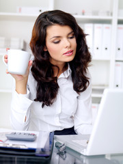 Young businesswoman working and drinking coffee