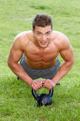 Muscular man working out on green grass