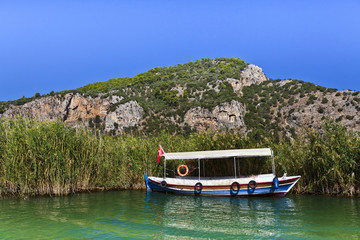 River boat by the historic Kaunian rock tombs in Dalyan, TURKEY.
