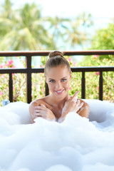 Smiling woman enjoying a relaxing bubble bath