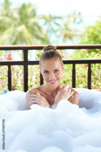 canvas print picture Smiling woman enjoying a relaxing bubble bath