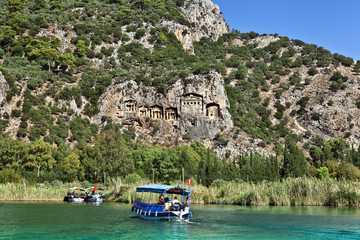 Tourist boats by the historic rock tombs in Dalyan, TURKEY.