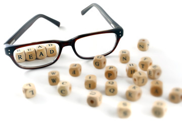 glasses and read message written in wooden blocks, isolated on w