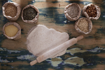 Grains, flour and rolling pin on wooden table