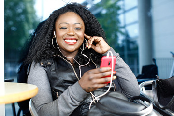 Vivacious African woman listening to music