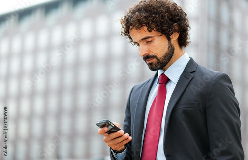canvas print picture Mature businessman using his phone