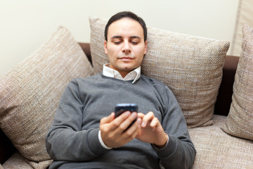 Relaxed man using phone on his sofa