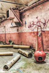 Red industrial fire extinguisher in an abandoned factory