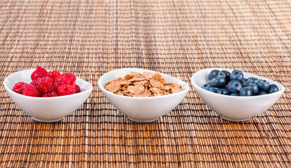 Bowls with blueberries, corn flakes and raspberries