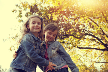 Two young girls having fun in the autumn sunny day