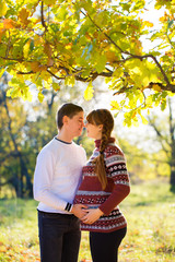 Beautiful Young Pregnant Couple Having Picnic in autumn Park. Ha