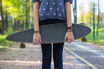 fashion young woman posing  with a longboard