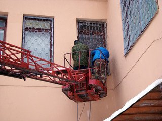 Workers cut lattice with Windows (instructed by fire inspection)