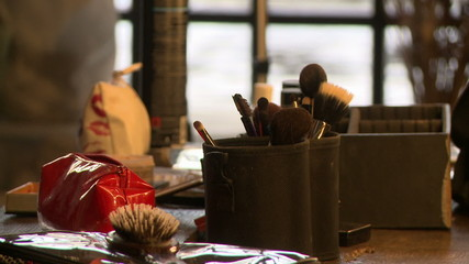 View of makeup artist puts brush in beautician