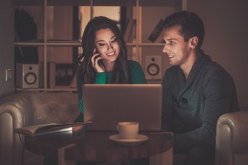Young couple behind laptop discussing something