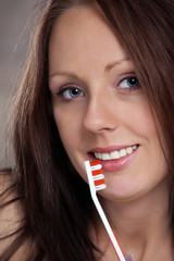 Pretty girl with healthy teeth, holding toothbrush
