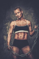 Beautiful muscular bodybuilder woman holding chains