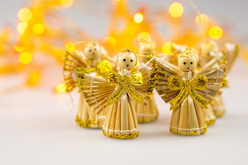 six straw christmas angels on white background with blurred yell