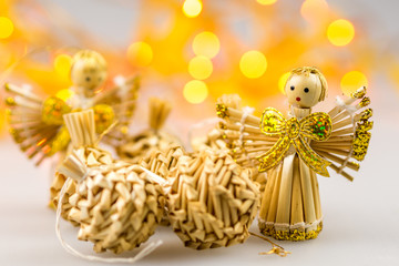 six straw christmas balls and two angels on white background wit