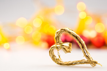 one straw christmas heart on white background with blurred yello