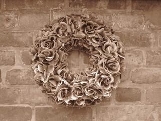Blumenkranz an Backsteinmauer im Sepia-Stil