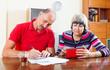 Sad senior couple calculating  budget