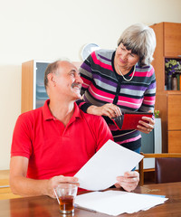 mature couple looking financial documents