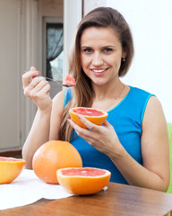 Pretty woman eats grapefruit