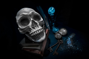 Skull on books and magic crystal balls with rusty keys