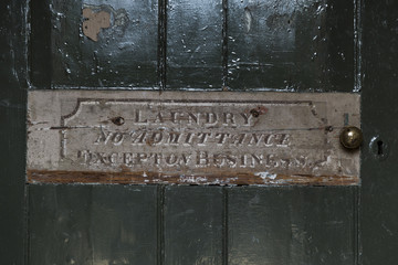 Laundry No Admittance Sign on Old Green Wooden Door