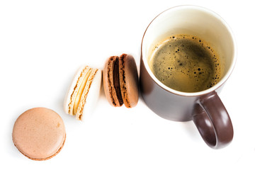 Mug of coffee and macaroons on a white background top view