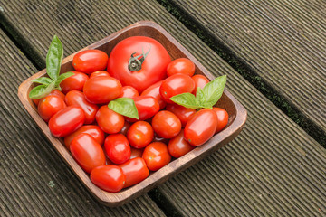 Tomatoes In A Wooden Bowl On Floorboards
