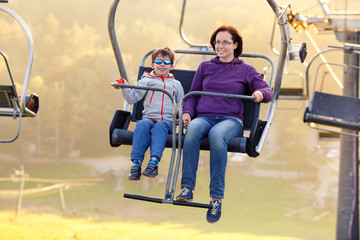 Happy mother and son ride chair lift