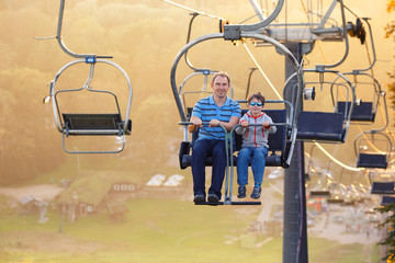 Happy father and son ride chair lift