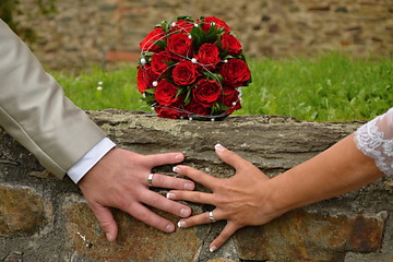 wedding bouquet of roses and hands