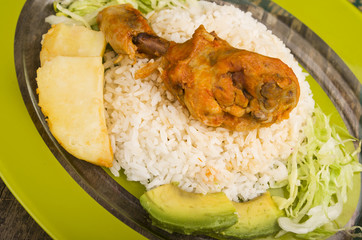 chicken served with white rice potato on a plate