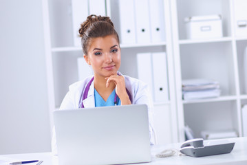 Female doctor sitting on the desk and working a laptop in