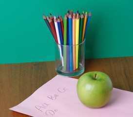 Pencils on a glasses, green apple and paper on the desk.