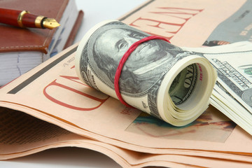 Dollars, an organizer and a pen on a newspaper, isolated on