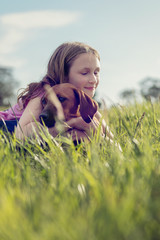 girl with her puppy in the grass