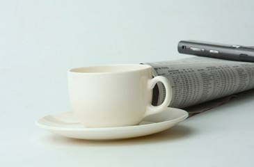 A cup of coffee, a mobile phone and a newspaper