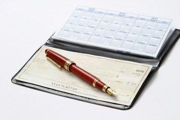 An open checkbook and a ballpen isolated on white