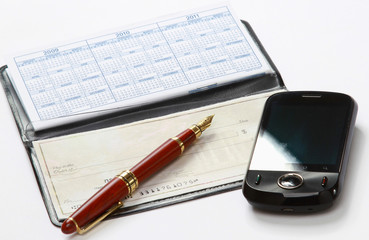 A pen and a mobile phone over a checkbook
