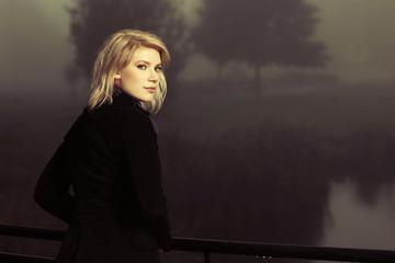 Young fashion woman against an autumn foggy landscape