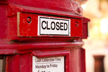 a closed red english letterbox.