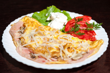 omelet with vegetables and tomatoes on wooden background