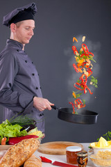 male chef tossing vegetables from wok in kitchen
